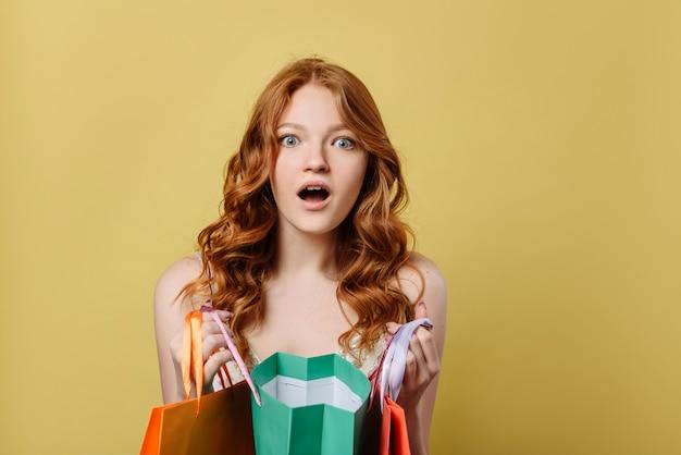 Jovem espantada com sacolas de compras.