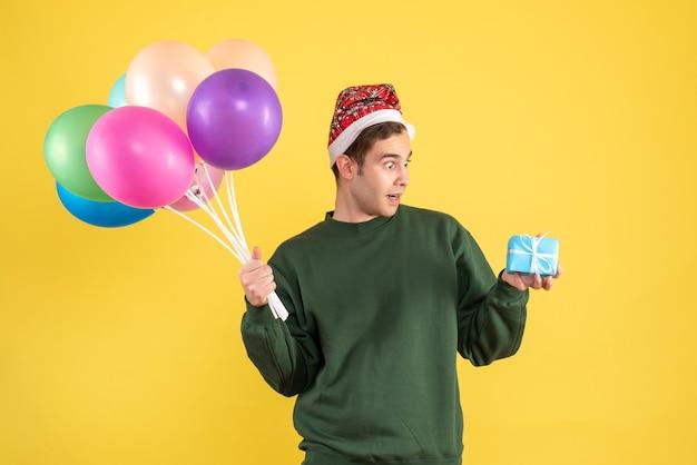 Jovem espantado de frente com chapéu de papai noel e balões coloridos em amarelo