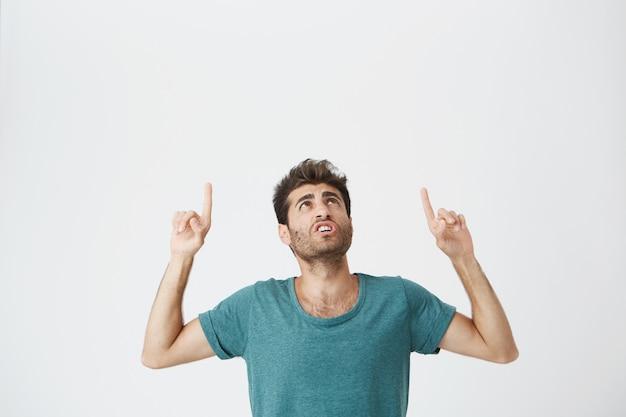 Jovem espantado elegante homem com barba, apontando os dedos na parede branca, com espaço de cópia para o seu anúncio ou informações promocionais