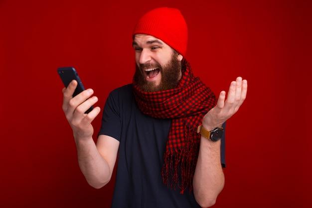 Jovem espantado está olhando no telefone perto da parede vermelha.