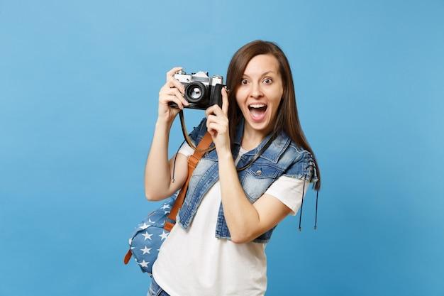 Jovem espantado estudante mulher animada em t-shirt branca, roupas jeans com mochila segurando a câmera fotográfica vintage retrô isolada sobre fundo azul. educação no ensino médio. copie o espaço para anúncio.