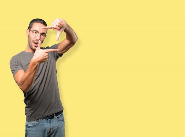 Jovem espantado, fazendo um gesto de tirar uma foto com as mãos