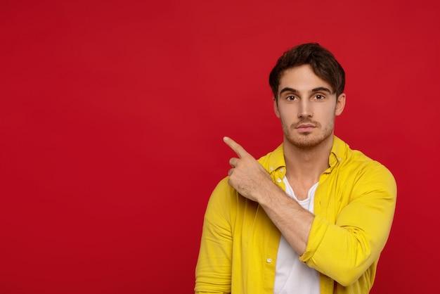 Jovem espantado na camisa amarela, apontando com o dedo de lado, não pode acreditar nos olhos, olha para a câmera