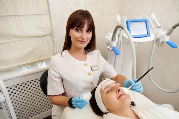 Jovem especialista em cosmetologia aplicando com escova máscara facial de beleza no rosto. tornando a pele hidratada e o rosto radiante.