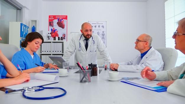 Jovem especialista médico discutindo sobre o diagnóstico do paciente com colegas de trabalho na sala de conferências do hospital. terapeuta especialista em clínica falando com colegas sobre doenças, profissional de medicina