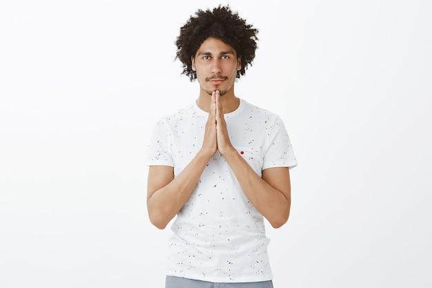 Jovem esperançoso orando, fechando os olhos e implorando com as mãos entrelaçadas