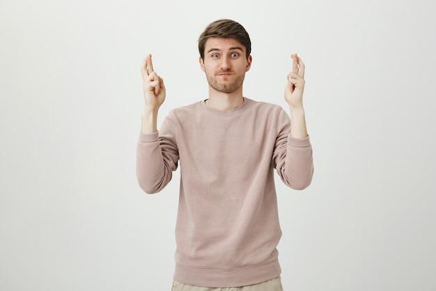 Jovem esperançoso relatando notícias, cruze os dedos boa sorte