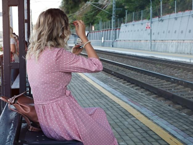 Jovem esperando na plataforma do trem consertando a maquiagem