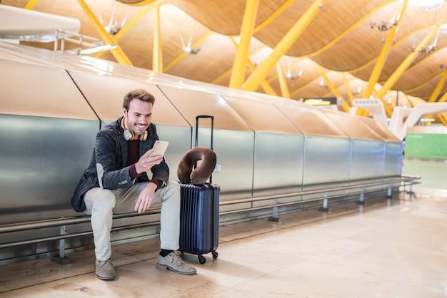 Jovem esperando ouvir música e usando telefone celular no aeroporto com uma mala.