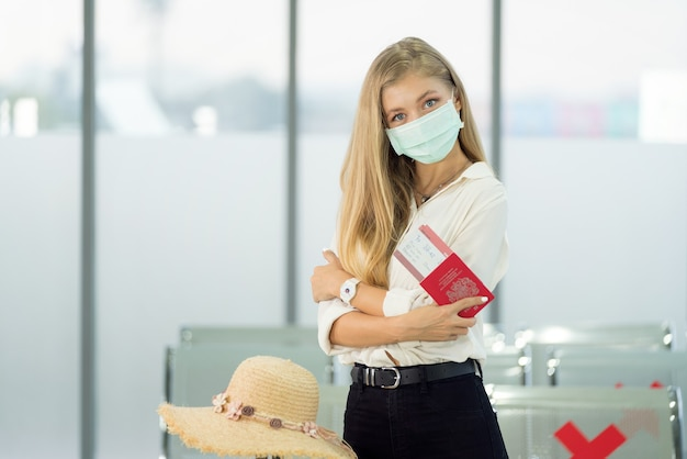 Jovem esperando para voar no aeroporto usando máscara