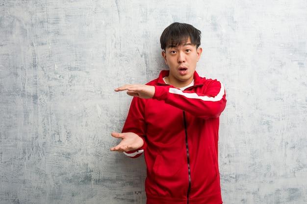 Jovem esporte fitness chinês segurando algo muito surpreso e chocado