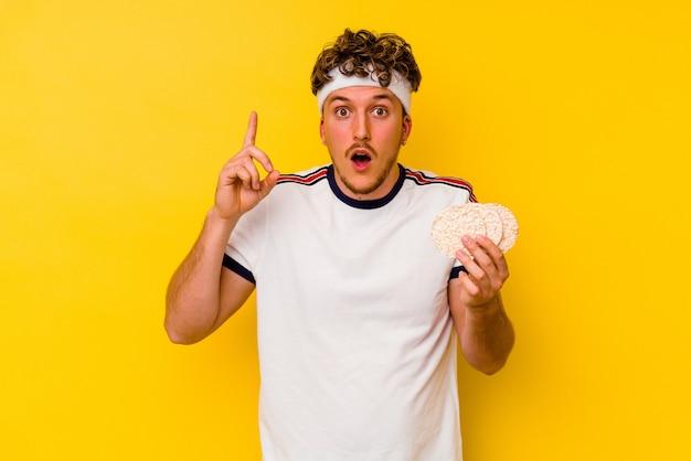 Jovem esporte homem caucasiano comendo um bolo de arroz isolado no fundo amarelo, tendo uma ideia, o conceito de inspiração.