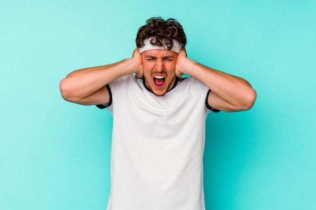 Jovem esporte homem caucasiano isolado em um fundo azul, cobrindo as orelhas com as mãos, tentando não ouvir o som muito alto.