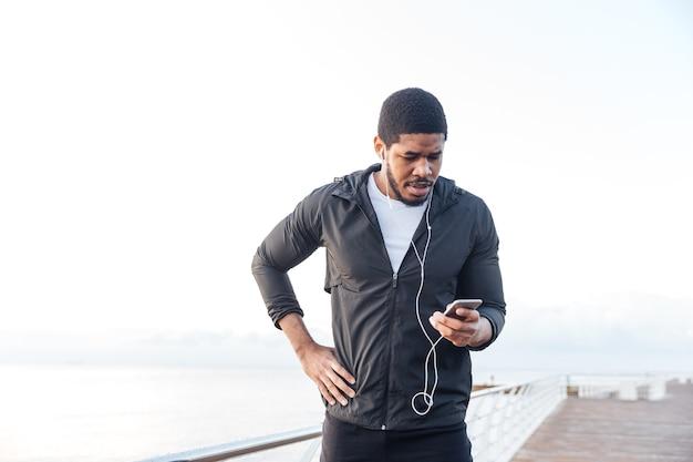 Jovem esportista africano concentrado ouvindo música em um telefone móvel no píer