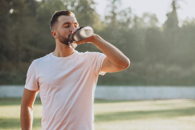Jovem esportista bebendo água no estádio