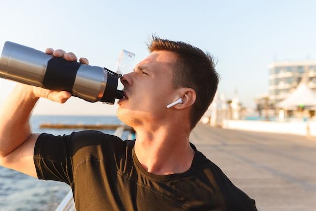 Jovem esportista cansado com fones de ouvido bebendo água