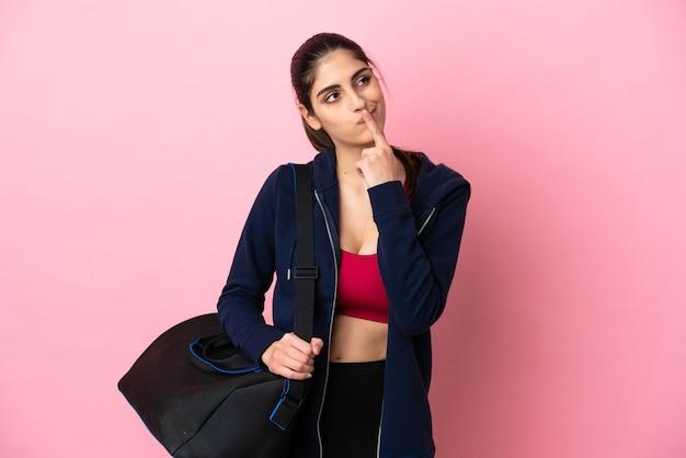 Jovem esportista caucasiana com bolsa esportiva isolada em um fundo rosa, tendo dúvidas enquanto olha para cima