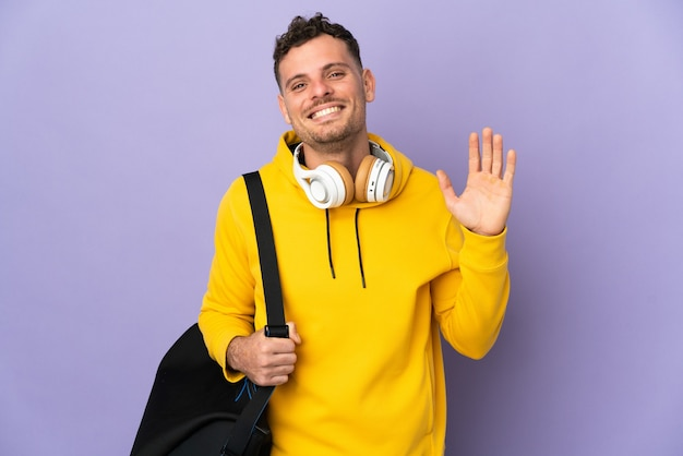 Jovem esportista caucasiano com bolsa isolada