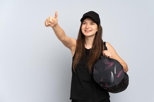 Jovem esportista com bolsa esporte isolada em cinza fazendo um gesto de polegar para cima