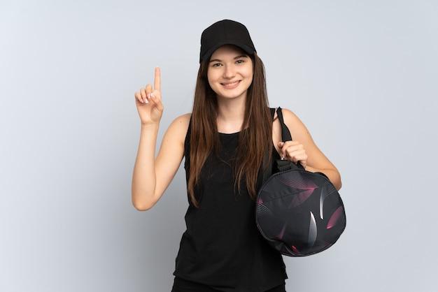 Jovem esportista com bolsa esportiva isolada em cinza apontando para uma ótima ideia