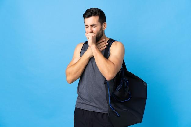 Jovem esportista com bolsa esportiva isolada em fundo azul, tossindo muito