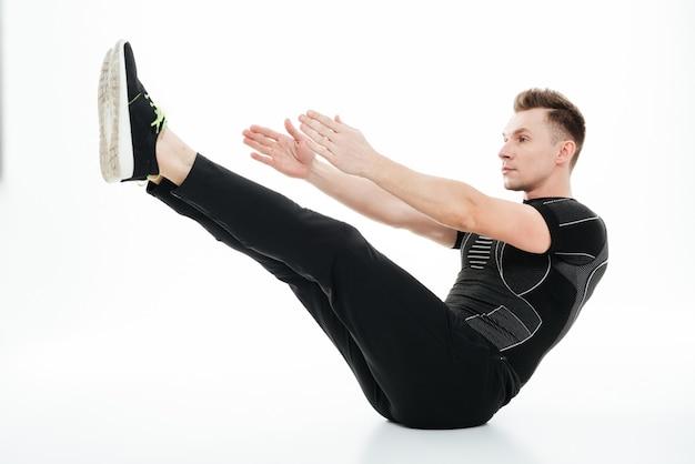 Jovem esportista concentrada fazendo exercícios abdominais no chão