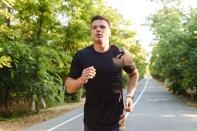 Jovem esportista confiante sem camisa usando fones de ouvido correndo
