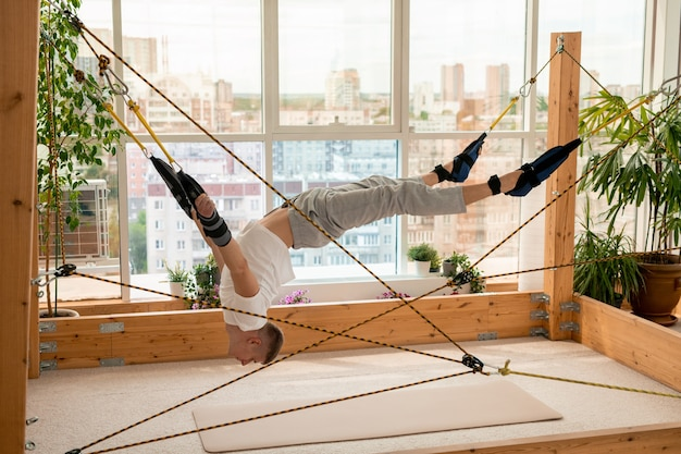 Jovem esportista contemporâneo com braços e pernas presos a cordas, fazendo difíceis exercícios de ioga aérea enquanto está pendurado no chão