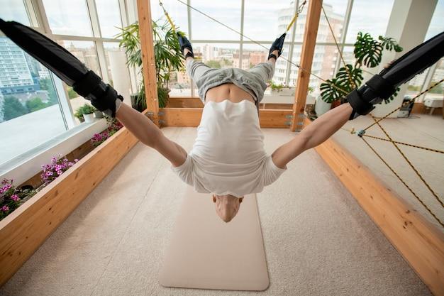 Jovem esportista contemporâneo curvando-se para trás com os braços e as pernas presos a cordas, fazendo exercícios de ioga aérea na academia ou em casa