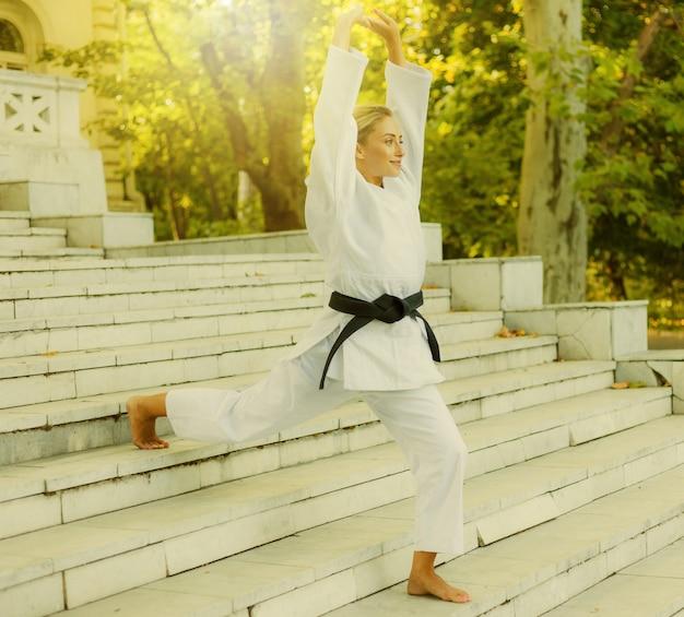 Jovem esportista de quimono branco com faixa preta faz aquecimento na escada antes do treino. artes marciais, autodefesa