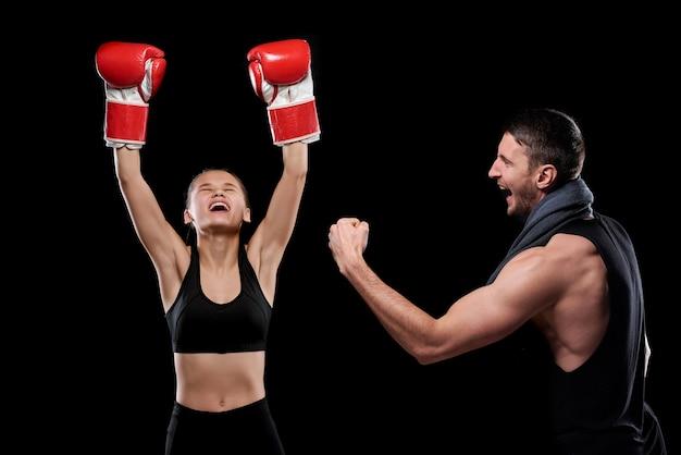 Jovem esportista em êxtase com luvas de boxe e roupas esportivas e seu treinador expressando triunfo após um jogo de sucesso