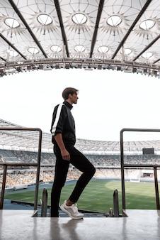 Jovem esportista em grande estádio de futebol vazio
