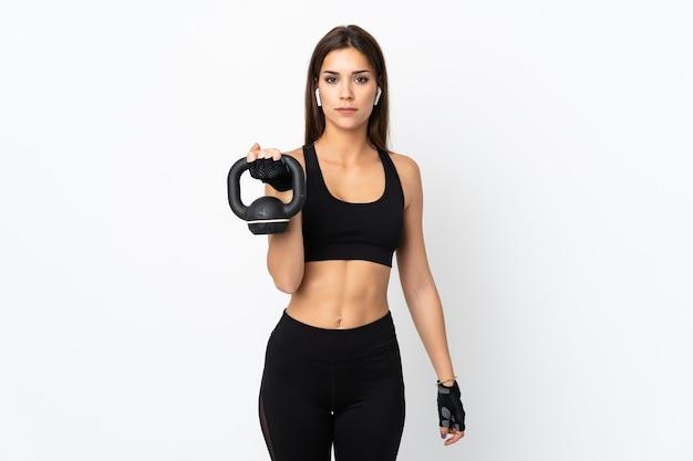 Jovem esportista fazendo levantamento de peso com kettlebell e olhando para frente