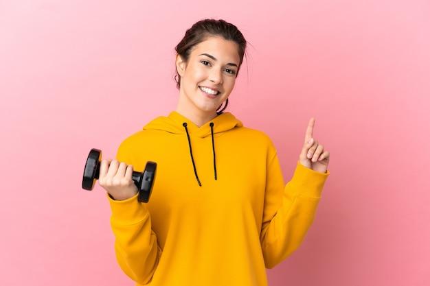Jovem esportista fazendo levantamento de peso sobre fundo rosa isolado, mostrando e levantando um dedo em sinal dos melhores