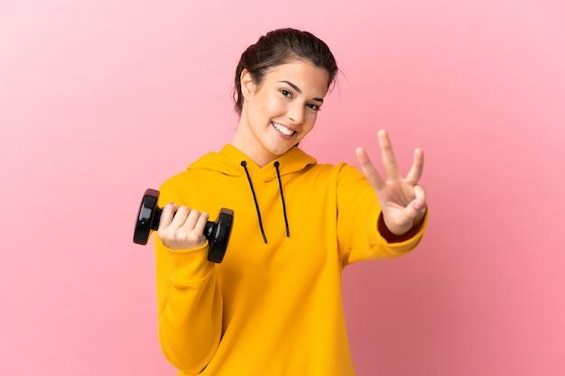 Jovem esportista fazendo levantamento de peso sobre um fundo rosa isolado feliz e contando três com os dedos