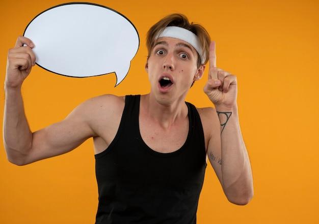 Jovem esportista impressionado segurando pontos de bolha do discurso isolados em uma parede laranja com espaço de cópia
