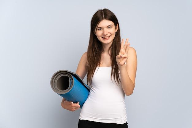 Jovem esportista indo para as aulas de ioga, segurando um tapete feliz e contando três com os dedos