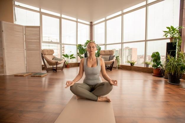 Jovem esportista loira ativa cruzando as pernas enquanto está sentada na esteira em pose de lótus e praticando exercícios de meditação em ambiente doméstico