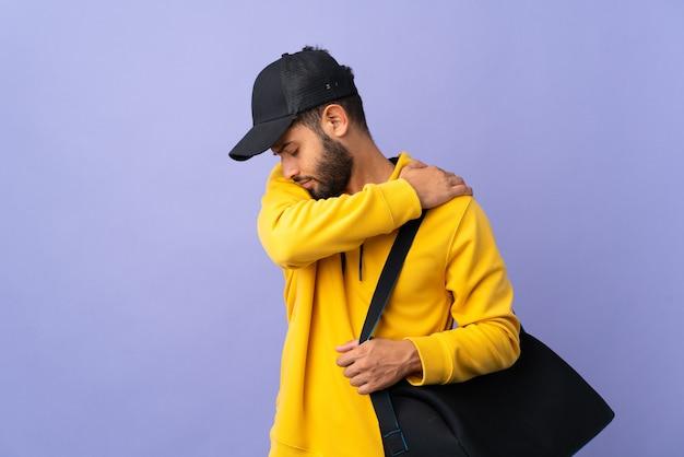 Jovem esportista marroquino com bolsa esportiva isolada na parede roxa, sentindo dor no ombro por ter feito um esforço