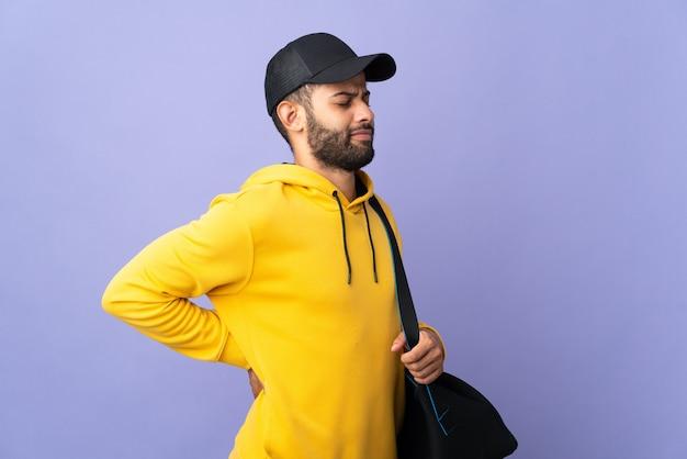 Jovem esportista marroquino com bolsa esportiva isolada na parede roxa, sofrendo de dor nas costas por ter feito esforço