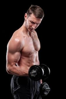 Jovem esportista musculoso sem camisa com halteres fazendo exercícios para os braços isolado sobre a parede preta