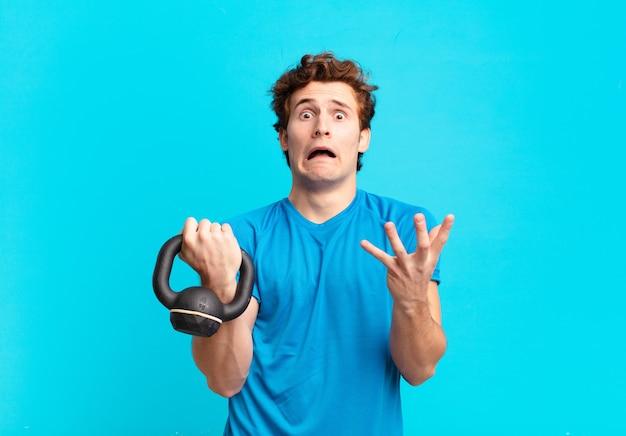 Jovem esportista parecendo desesperado e frustrado, estressado, infeliz e irritado, gritando e gritando. conceito de haltere