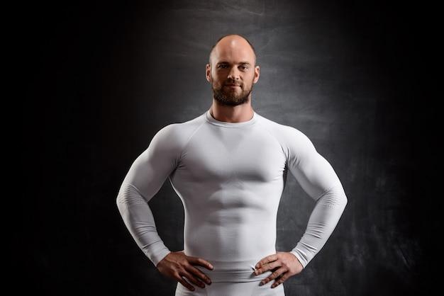 Jovem esportista poderosa em roupas brancas sobre parede preta.