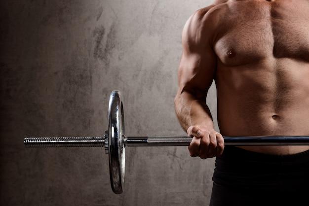 Jovem esportista poderosa treinando com barra sobre parede escura.