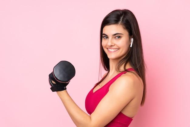 Jovem esportista sobre rosa isolada fazendo levantamento de peso