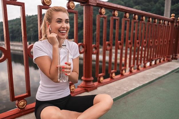 Jovem esportista sorridente usando fones de ouvido sem fio e relaxando ao ar livre na ponte enquanto segura uma garrafa de água