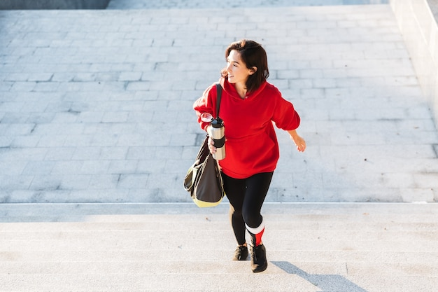 Jovem esportista sorridente, vestindo um moletom, caminhando ao ar livre, carregando uma sacola esportiva e segurando uma xícara de café