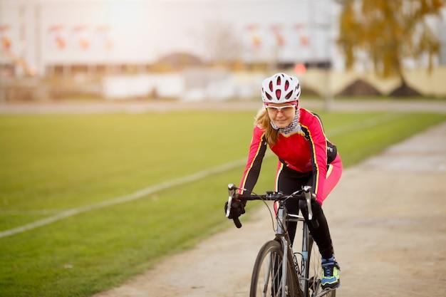 Jovem esportiva andando de bicicleta em treinamento no parque
