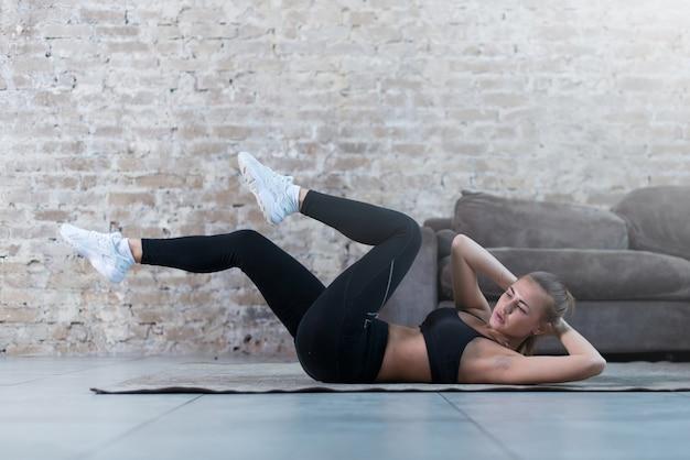 Jovem esportiva fazendo exercício de trituração cruzada, deitado sobre um tapete no estúdio moderno