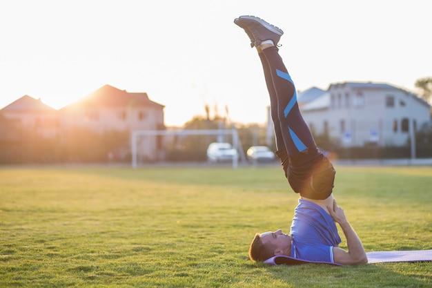 Jovem esportiva fazendo exercícios no campo de manhã ao ar livre